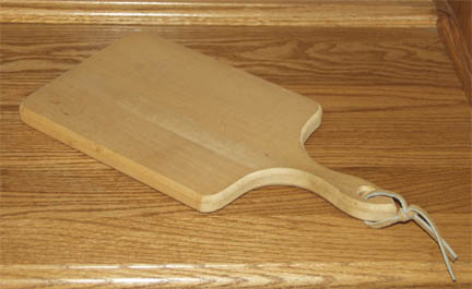 Hardwood cutting board with leather thong to hang it